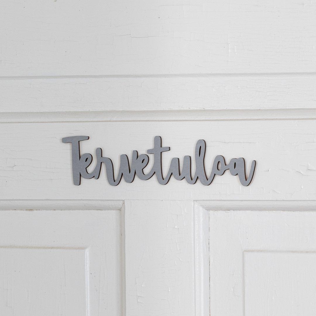 Puine Piela tervetuloa ovikyltti harmaa koivuvanerista valkoisessa ovessa lähikuva