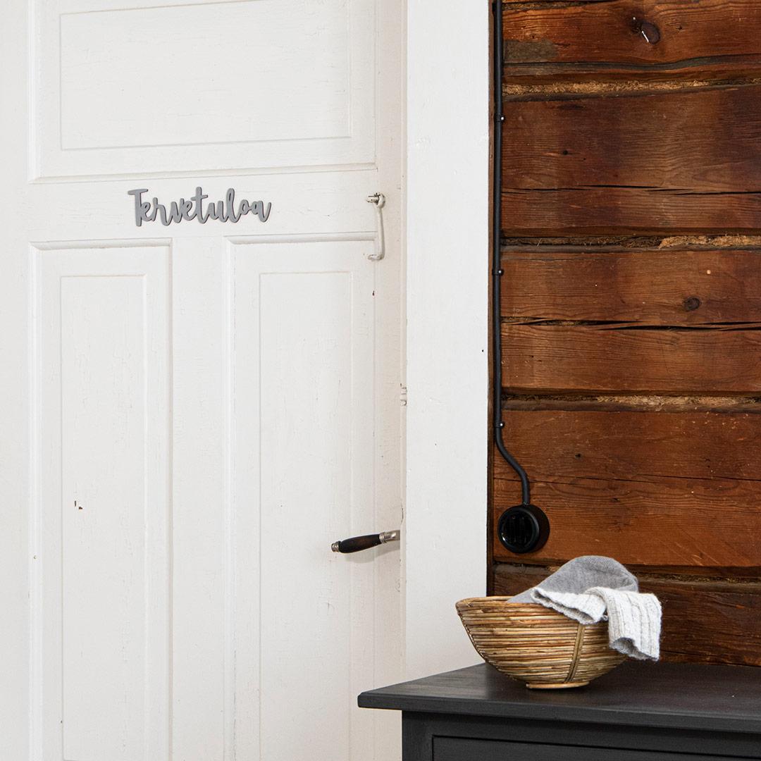 Puine Piela tervetuloa ovikyltti harmaa koivuvanerista valkoisessa ovessa