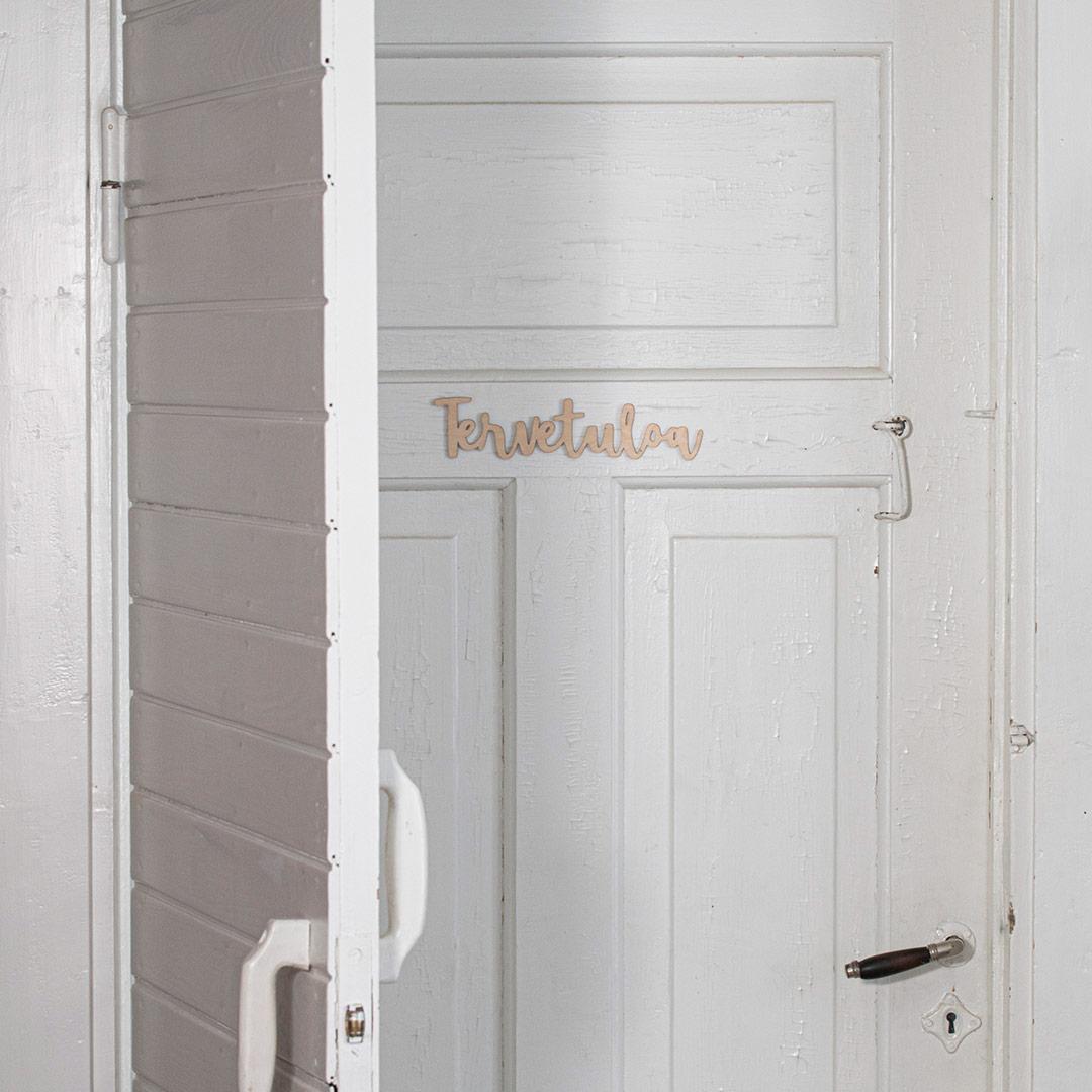 Piela tervetuloa ovikyltti koivuvanerista valkoisessa ovessa