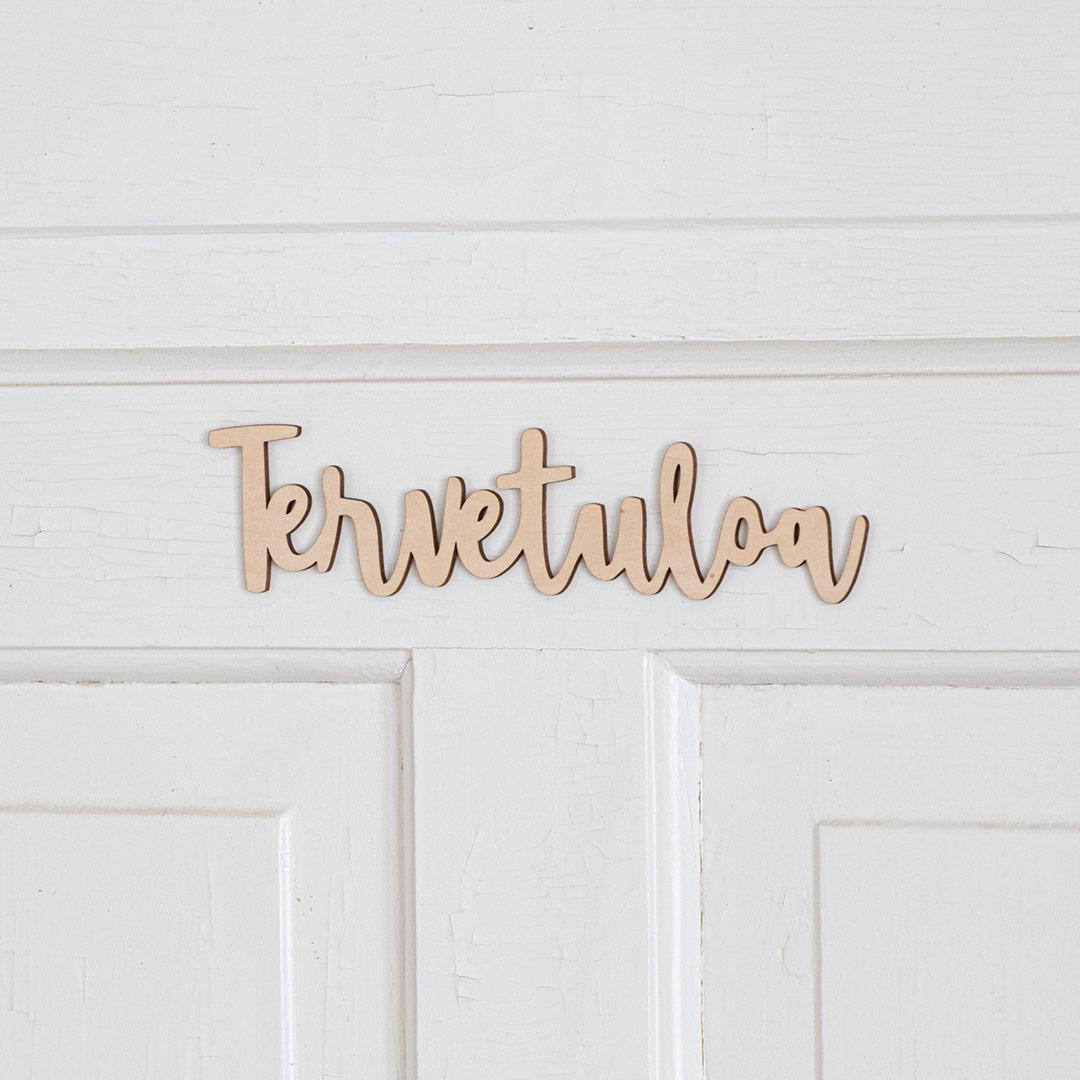 Puine Piela tervetuloa ovikyltti koivuvanerista valkoisessa ovessa lähikuva