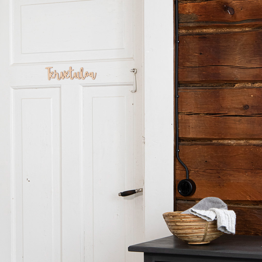 Puine Piela tervetuloa ovikyltti koivuvanerista valkoisessa ovessa