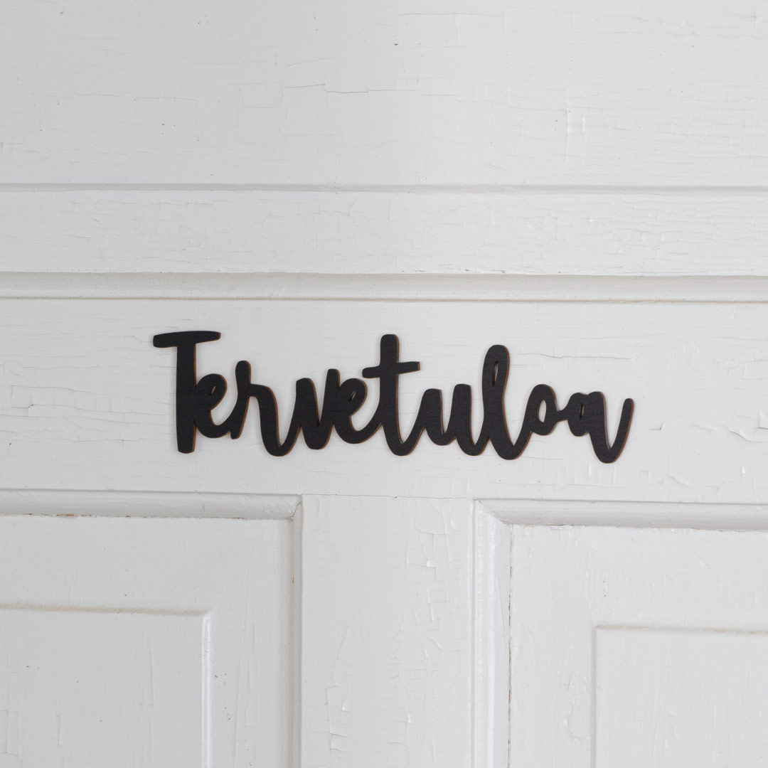 Puine Piela tervetuloa ovikyltti musta valkoisessa ovessa lähikuva