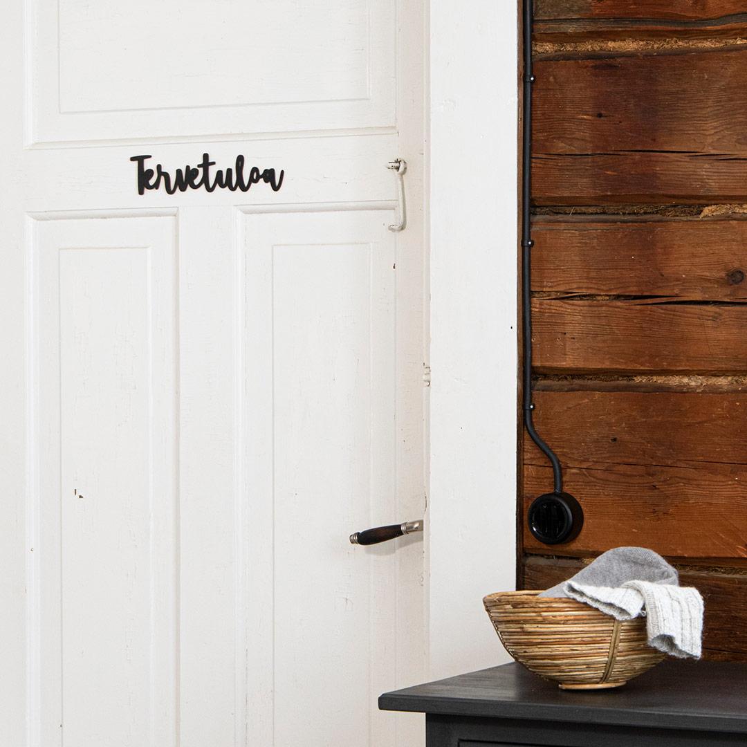 Puine Piela tervetuloa ovikyltti musta valkoisessa ovessa