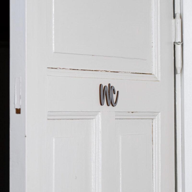 Puine Piela ovikyltti wc koivuvanerista harmaa huussin ovessa lähikuva