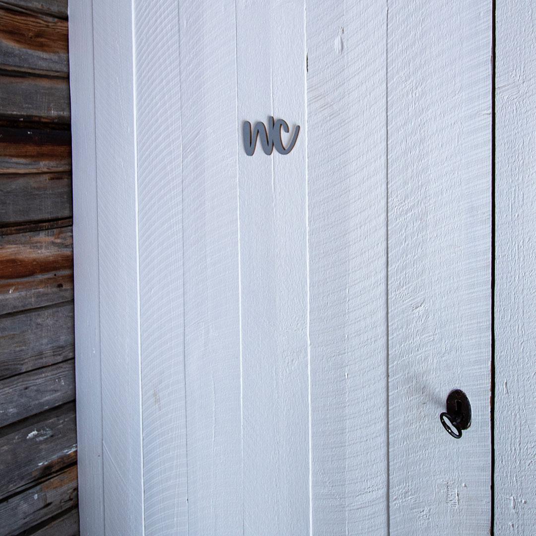 Puine Piela ovikyltti wc koivuvanerista harmaa huussin ovessa