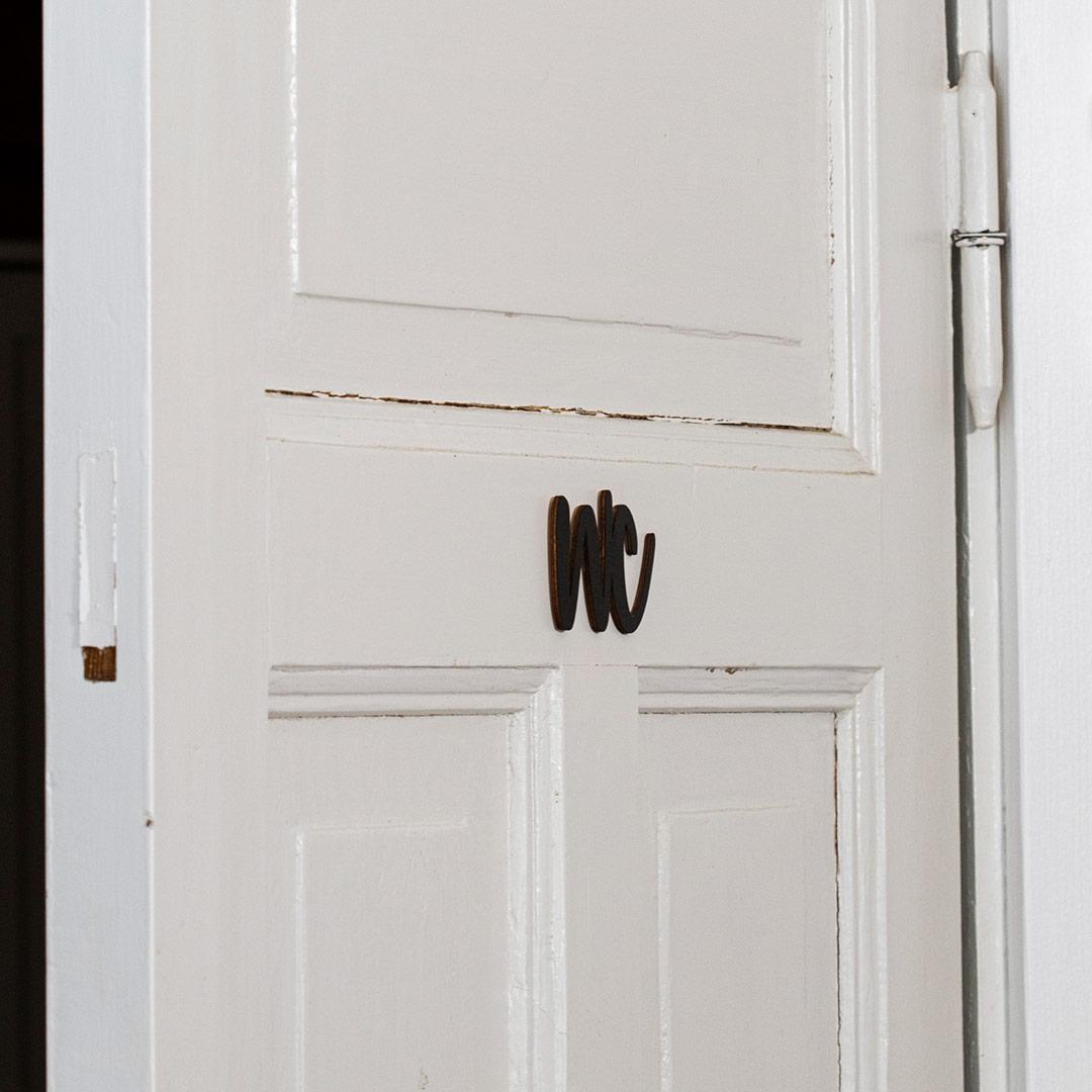 Puine Piela ovikyltti wc koivuvanerista musta valkoisessa vessan ovessa