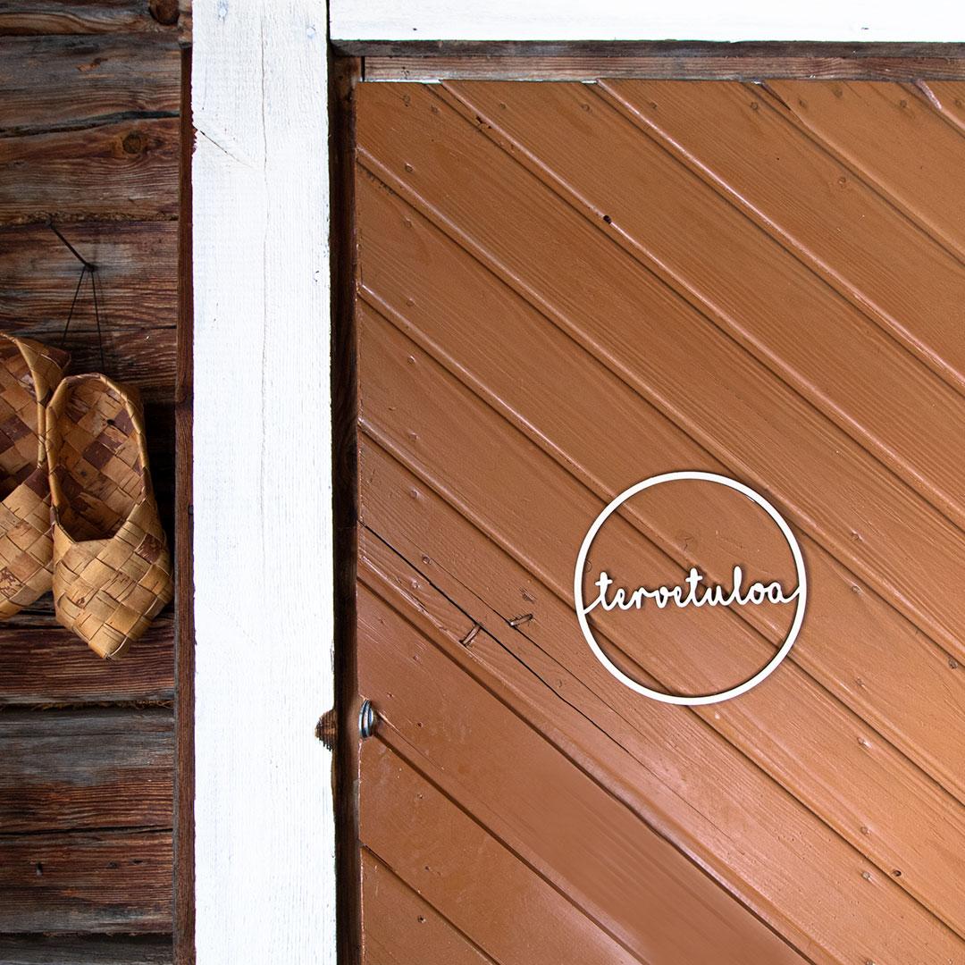 Puine tervetuloa kranssi koivuvaneri valkoinen saunatuvan ovessa